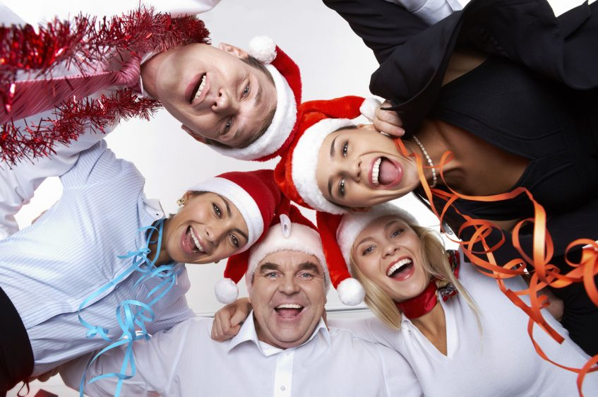 Portrait of smart colleagues in Santa caps wishing you Merry Christmas